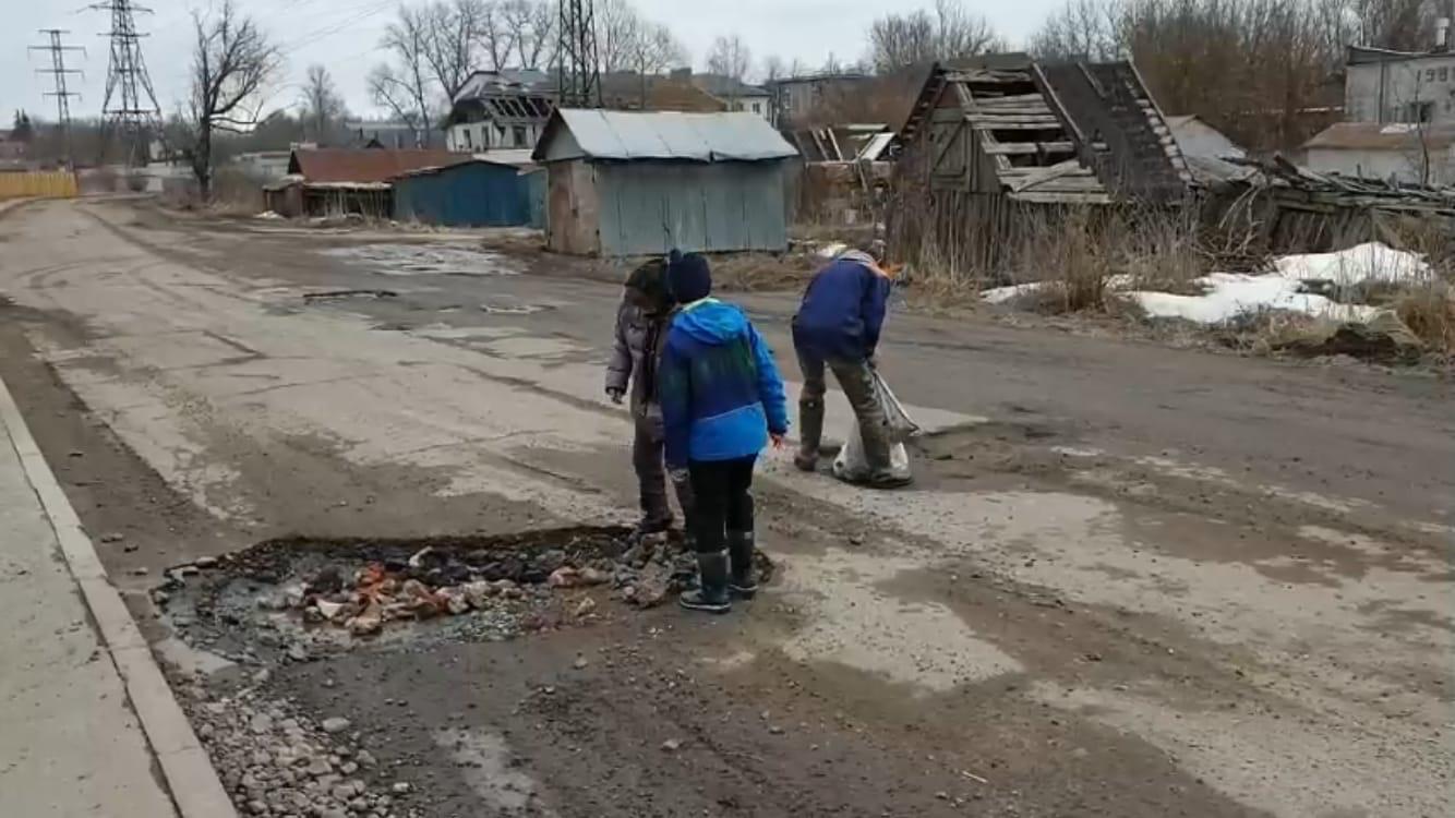 В поселке Белые Берега дети сами заделали ямы на дорогах
